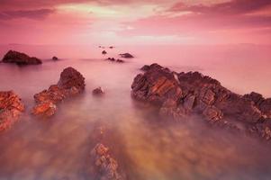 praia rochosa ao pôr do sol. foto