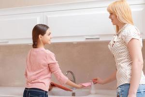 mãe e filha lavam pratos