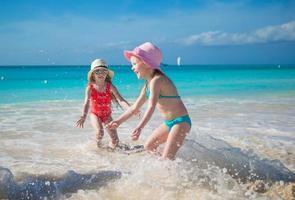 adoráveis garotinhas brincando em águas rasas em uma praia exótica foto