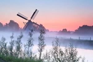 encantador moinho holandês ao nascer do sol