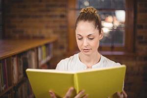 professora loira lendo livro na biblioteca foto