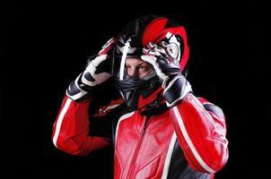 motociclista segurando seu capacete com as duas mãos