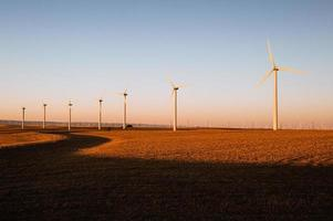 turbinas produzindo energia eólica em um belo pôr do sol dourado foto