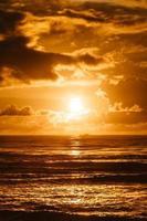 pôr do sol brilhante sobre a água do mar foto