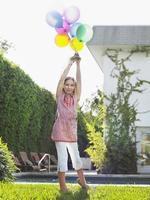 jovem segurando balões no gramado