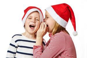 menina e menino com chapéu de Papai Noel foto