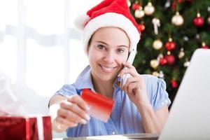 jovem e bonita mulher atraente segurando um cartão de crédito da internet foto