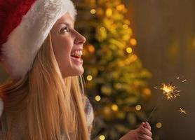 retrato de uma adolescente sorridente com chapéu de Papai Noel segurando estrelinhas