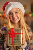 adolescente sorridente com chapéu de Papai Noel segurando uma caixa de presente de natal