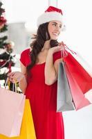 morena de vestido vermelho segurando sacolas de compras