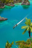 barco cruzando pequenas ilhas verdes pertencentes à ilha fam foto
