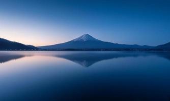 montanha fuji ao amanhecer com reflexão pacífica do lago