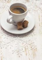 xícara de café, floco de neve em fundo branco de madeira foto