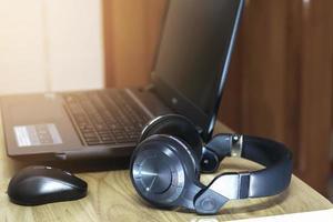 fones de ouvido ao lado do computador