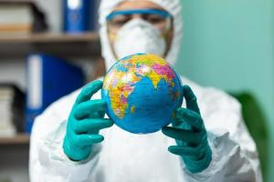 homem com traje de proteção branco segurando um globo terrestre