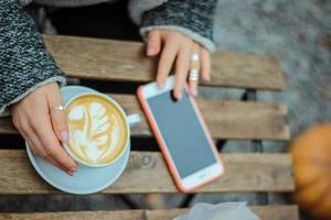mulher sentada à mesa com café com leite e telefone celular foto