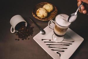 uma colher de espuma sobre uma bebida de café
