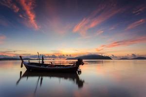 silhuetas de barco longtail e nascer do sol em phuket, Tailândia foto