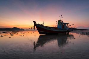 barco de pesca sentado na praia em areia phuket tailândia foto