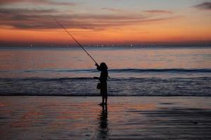 pescador solitário ao pôr do sol