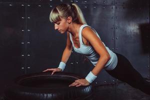 desportista. atleta desportiva em forma fazendo flexões no pneu foto