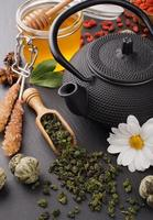 natureza morta com chá verde e mel sobre pedra negra