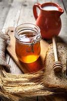 mel em uma jarra, fatia de pão, trigo e leite