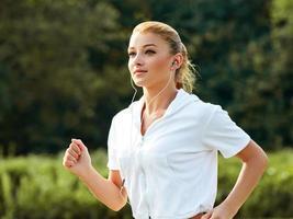 corredor atlético treinando em um parque. garota fitness correndo ao ar livre foto