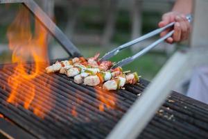 marisco misto grelhado na brasa em chamas de churrasco.