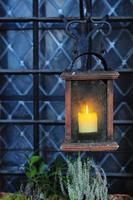 lanterna de madeira velha com vela perto da janela