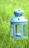 lanterna azul, com uma vela acesa dentro, na grama verde