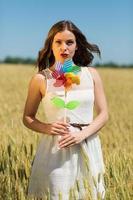 garota feliz com um moinho de vento colorido
