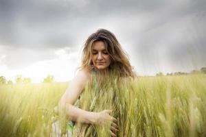 bela senhora abraçando espigas de trigo ao ar livre