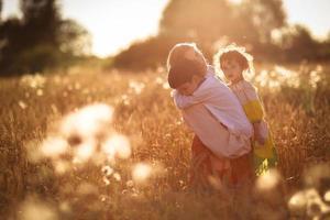 mãe com filho e filha nas mãos de um trigo foto