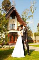 noiva e noivo no fundo de uma bela casa foto