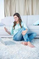 Mulher bonita usando seu smartphone e laptop