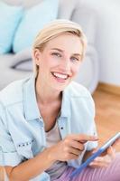 mulher loira bonita usando seu tablet no chão