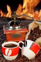 duas xícaras de café expresso, grãos de café e moedor