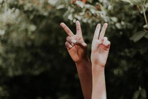 duas pessoas multiétnicas mostrando um símbolo da paz