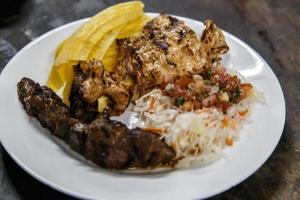 cozinha tradicional nicaraguense, carnes assadas, saladas e banana frita. foto