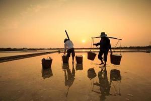 campo de sal no pôr do sol ou amanhecer, com silhueta pode gio foto