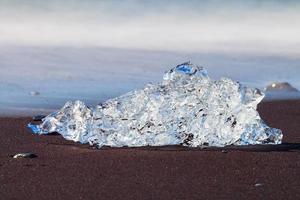 icebergs em praia negra cristalina foto