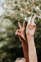 duas pessoas fazendo o sinal da paz ao ar livre