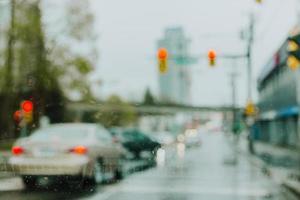carros desfocados em um semáforo em um dia chuvoso foto
