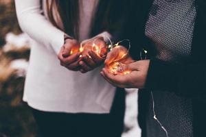 close-up de duas pessoas segurando luzes de corda iluminadas