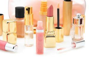 batons, brilho labial e perfumes em fundo branco foto