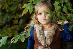 menina adorável com folhas de outono no parque
