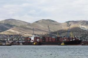 navio de carga marinho em um fundo de montanhas foto