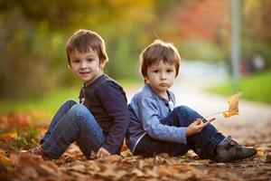 meninos adoráveis com folhas de outono no parque de beleza foto
