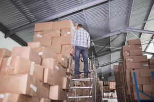 vista traseira do trabalhador na escada do armazém foto